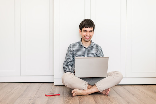 Smilling young man working with laptop at home. freelancer