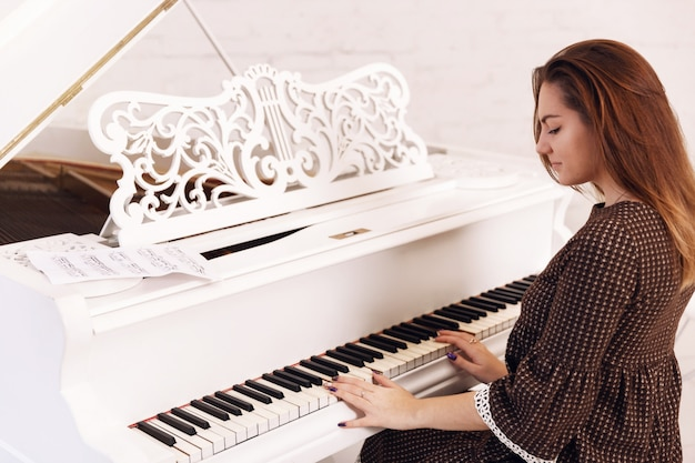 Smilling young woman playing the piano