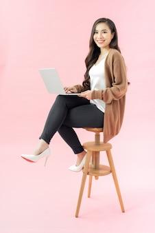 파란색 배경에 격리된 노트북 컴퓨터를 사용하여 웃고 있는 젊은 여성