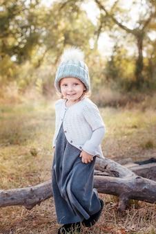 幸せな子供の女の子smillingと秋の屋外で遊ぶ