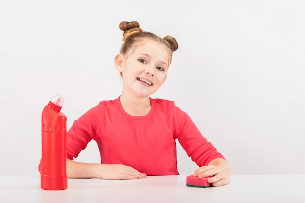 Smilng girl with a red cleaner and sponge