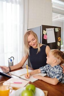 Улыбающаяся молодая мать с цифровым планшетом смотрит на своего сына, который делает домашнее задание и пишет в своем учебнике за кухонным столом