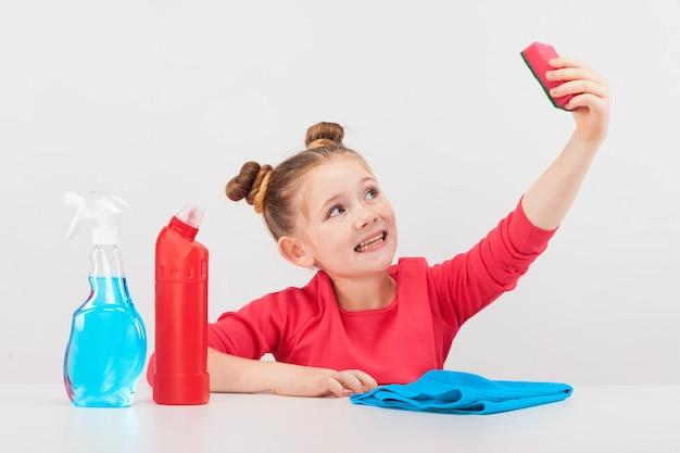 Smilng девушка с разноцветными чистящими средствами на белом