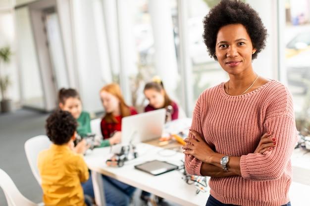 ロボット工学の教室で電気のおもちゃとロボットをプログラミングする子供たちのグループを持つスミリーアフリカ系アメリカ人の女性科学教師