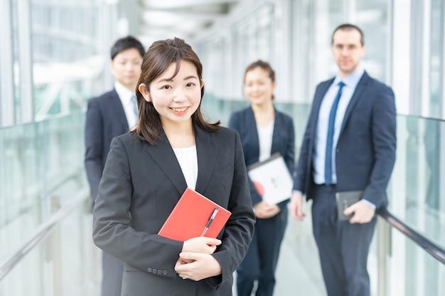 立っているスマイリーアジアのビジネスウーマンと彼女のビジネスチーム