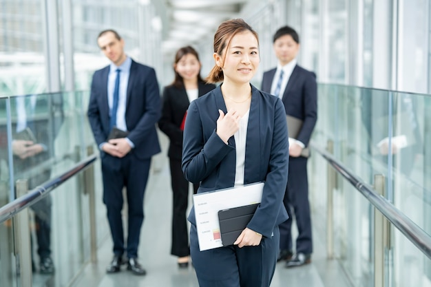 Smily asian business woman standing and her business team