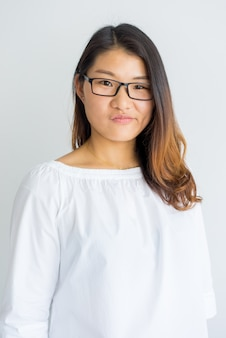 Smirking young chinese woman in eyeglasses looking at camera.