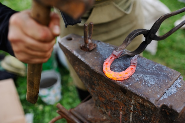 The smith makes a horseshoe on the anvil