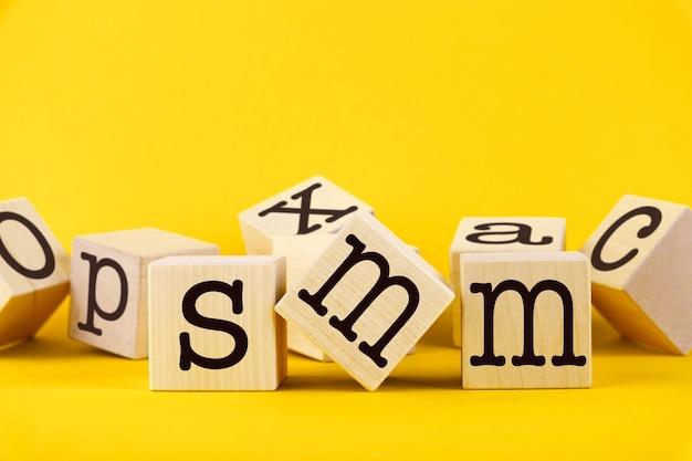 黄色の背景に木製の立方体に書かれた smm