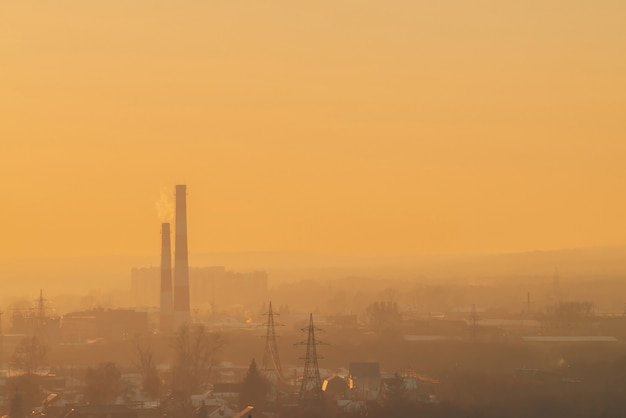 Smog among silhouettes of buildings on sunrise.