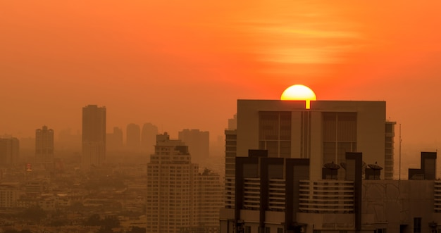 Smog and fine dust of pm2.5 covered city in the morning with orange sunrise sky. cityscape with polluted air.