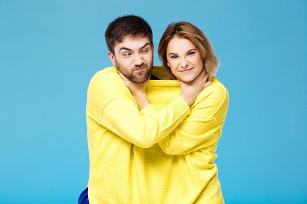 青い壁の上にお互いをsmohering若い美しいカップル