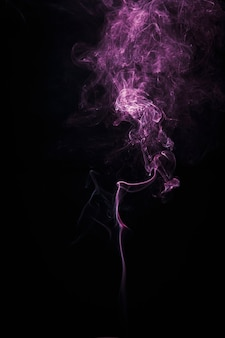 Smoke colorful floating in the air on dark background