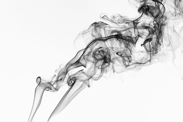 白い背景の上の空中に浮かぶカラフルな煙を吸う