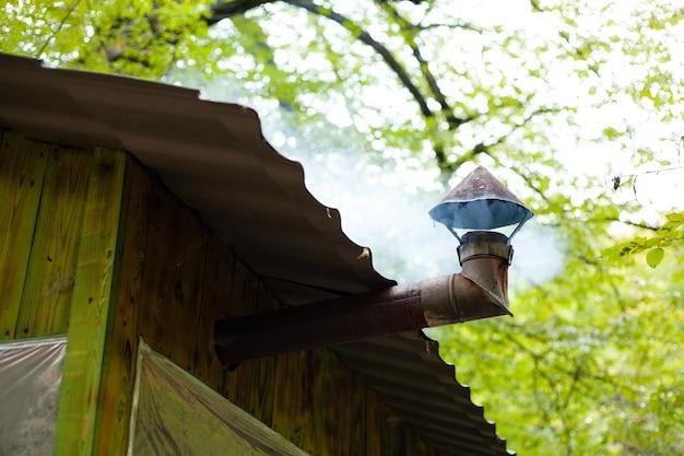 연기가 숲에 있는 목조 주택에서 나온다