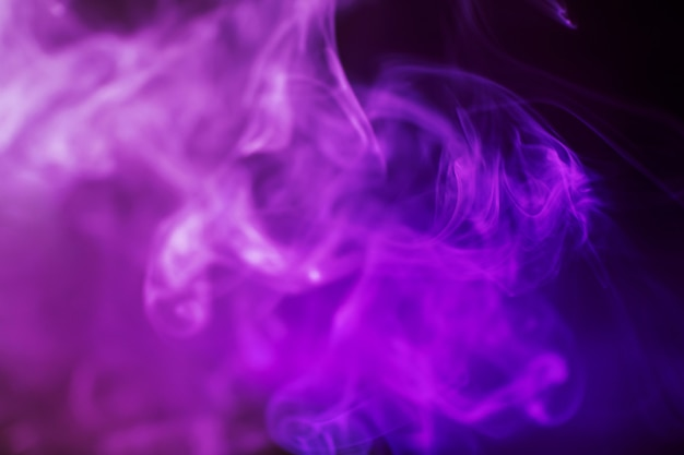 Smoke on a dark background in a bright trendy purple neon light.