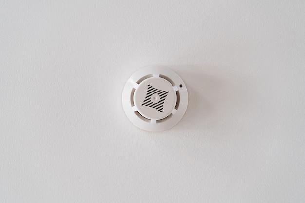 白い天井の煙探知器。火災警報。緊急時の家の保護。