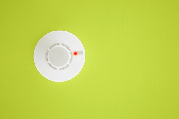 Smoke detector on yellow background. security system.