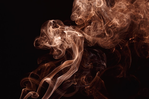 Smoke floating in the air on dark background. rose gold color