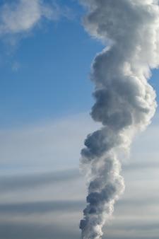 Дым из трубы на фоне неба. отопительный сезон зимой.