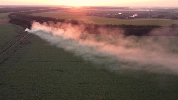 都市の外で燃えるごみからの煙、空撮、環境汚染。