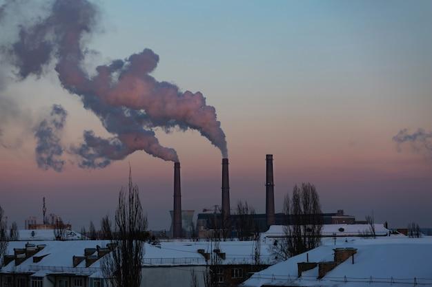 겨울 도시에서 공장 굴뚝에서 연기