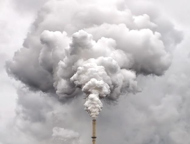 Дым из заводской трубы на фоне темного пасмурного неба