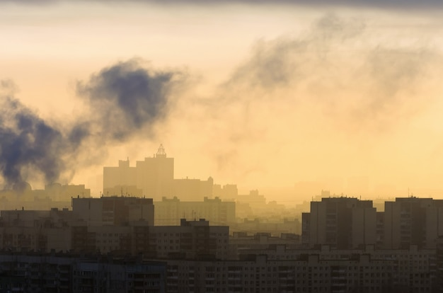 Smoke from industrial chimneys at dawn city.