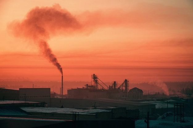 Smoke from pipe pollutes environment in dawn. storage of goods in warehouses in winter. view from above of industrial area in sunrise in pink tones. industrial buildings zone close up with copyspace.