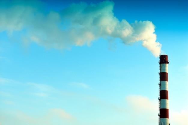 青い空を背景に煙突から煙が出る