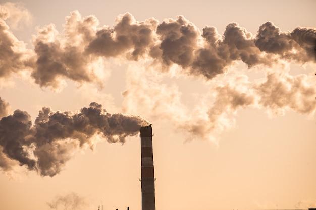 Дым из трубы на заводе на фоне заката