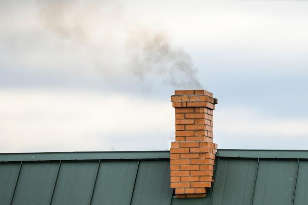Дым из трубы, отопление. вздымающийся дым. выходит из дымохода дома на фоне голубого неба