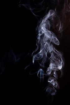 Движение дыма на черном фоне.