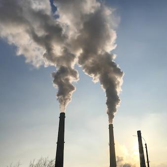 煙、日没に対する工場の工業用パイプからの汚染