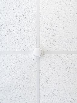 Датчик дыма на потолке в офисном помещении элемент пожарной сигнализации охрана рабочего места