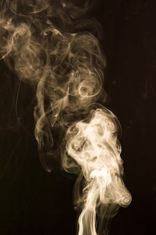 Smoke spread out wide over dark background