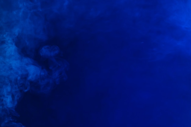 Smoke spreading on blue background