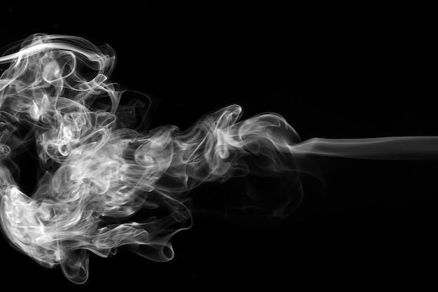 Smoke the white incense on a black background. fire design and darkness concept