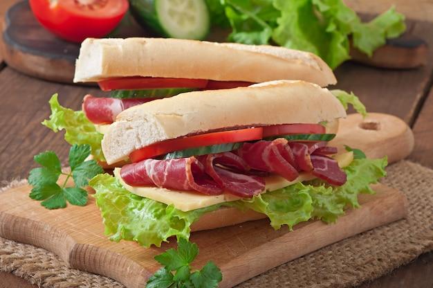 木製の背景に生のsmoke製肉と大きなサンドイッチ