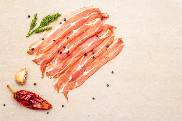 Smoked bacon slices with dried chili pepper, herbs and spices