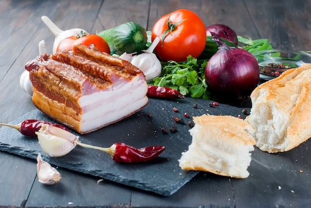 Smoked bacon with baguette and vegetables on stone black board