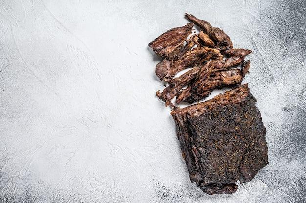 훈제 바베큐 쇠고기 양지머리 고기 스테이크. 흰 바탕. 평면도. 공간을 복사합니다.