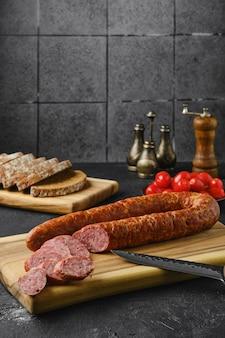 Колбаски копченой говядины на деревянной разделочной доске на кухонном столе