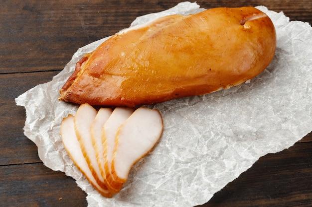 Копченая куриная грудка на коричневой деревянной доске