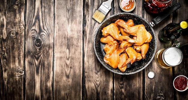 Копченые куриные крылышки с пивом и соусом. на деревянном столе.