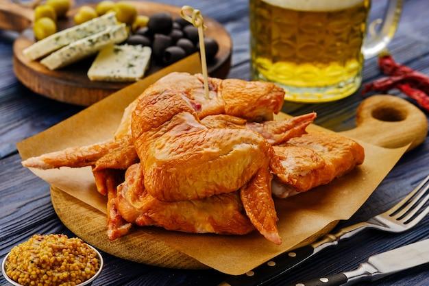Копченые куриные крылышки с пивом на деревянном столе.