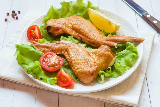 Smoked chicken wings with fresh lettuce tomato and lemon. copy space.