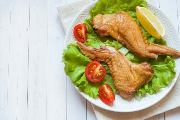 Smoked chicken wings with fresh lettuce tomato and lemon. copy space