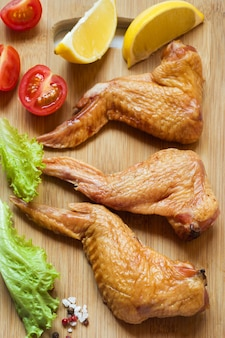 Smoked chicken wings with fresh lettuce tomato and lemon.