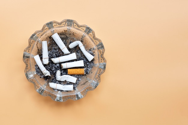 Smoked cigarettes on cream color background.